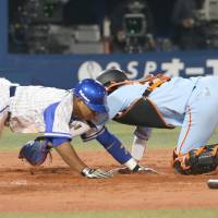 Yokohama's Jose Lopez (left) dives home before Yomiuri catcher Seiji Kobayashi can make the tag in the seventh inning of the BayStars' 6-3 win on Wednesday night. | KYODO
