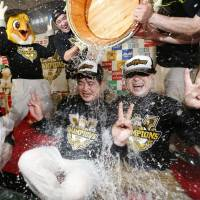 SoftBank owner Masayoshi Son (right) and Hawks manager Kimiyasu Kudo are doused with sake after the team clinched its second straight Japan Series title on Oct. 29, 2015. | KYODO