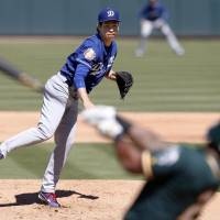 Los Angeles starting pitcher Kenta Maeda delivers during a spring training game against the Athletics in Mesa, Arizona, on Wednesday. | KYODO