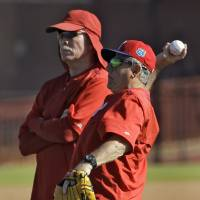 Philadelphia Phillies guest instructor Mike Schmidt (left) and coach Larry Bowa watch the team practice during spring training last month in Clearwater, Florida. | AP