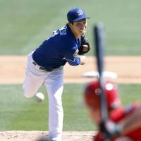 Los Angeles' Kenta Maeda delivers during the Dodgers' 7-6 preseason loss to the Reds on Sunday. | KYODO