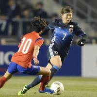 Nadeshiko Japan's Yuri Kawamura attempts to get by a South Korean player during their match on Wednesday in Osaka.   KYODO