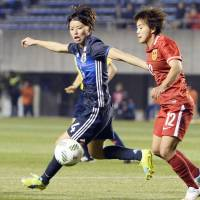 Japan's Saki Kumagai (left) and China's Wang Shuang vie for the ball during their Asian qualifier for the Rio de Janeiro Olympics on Friday in Osaka. China defeated Japan 2-1 at Kincho Stadium.   KYODO