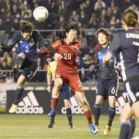 Yukari Kinga heads the ball during Nadeshiko Japan's 2-1 loss to China in their Asian final qualifier in Osaka on Friday night. | KYODO