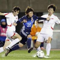 Nadeshiko Japan's Kumi Yokoyama (center) takes on two North Korean defenders during their 2016 Rio Games qualifying match in Osaka on Wednesday. Japan won 1-0. | KYODO