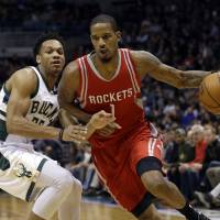 Houston's Trevor Ariza drives around Milwaukee's Rashad Vaughn in the first half on Monday night. The Bucks won 128-121. | AP