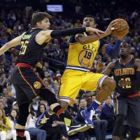 Golden State's Leandro Barbosa (center) drives to the basket as Atlanta's Kyle Korver (left) defends during Golden State's 109-105 win on Tuesday. | AP