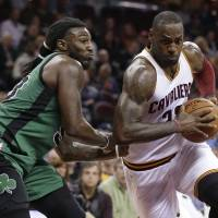 Cavaliers forward LeBron James drives past the Celtics' Jae Crowder on Saturday. | AP