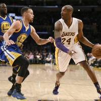 Lakers guard Kobe Bryant works against the Warriors' Stephen Curry on Sunday. | AP