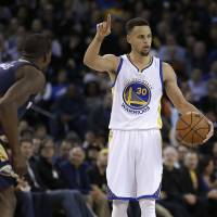 Golden State's Stephen Curry calls a play while guarded by New Orleans' Toney Douglas in the second half on Monday night. | AP