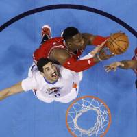 Oklahoma City's Enes Kanter (below) vies for a rebound with Houston's Dwight Howard (above) and Trevor Ariza during the Thunder's 111-107 win on Tuesday. | AP