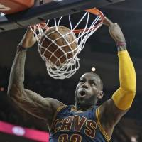 LeBron James dunks during the Cavaliers' win over the Bucks on Wednesday in Cleveland. | AP