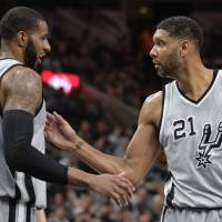 Throughout his legendary career, Spurs big man Tim Duncan (right), seen congratulating teammate LaMarcus Aldridge during a recent game, has been the consummate professional. | AP