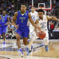 North Carolina's Joel Berry tries to steal the ball from Florida Gulf Coast's Julian DeBose in their first-round NCAA Tournament game on Thursday. North Carolina won 83-67. | USA TODAY / REUTERS