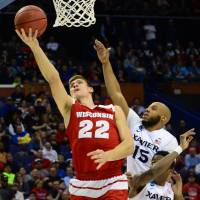 Wisconsin's Ethan Happ attempts a shot while being defended by Xavier's Myles Davis (4) and Edmond Sumner during their NCAA Tournament game on Sunday. | USA TODAY / REUTERS