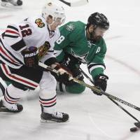 Dallas' Vernon Fiddler (right) sweeps the puck away from Chicago's Tomas Fleischmann in the first period on Friday night. The Stars defeated the Blackhawks 5-2. | AP