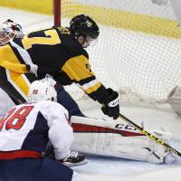 The Penguins' Bryan Rust scores past Capitals goalie Braden Holtby during the first period on Sunday in Pittsburgh. | AP