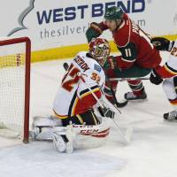 Minnesota's Zach Parise (right) scores past Calgary goalie Niklas Backstrom in the first period on Thursday night. | AP