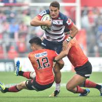 Melbourne's Mitch Inman is tackled by the Sunwolves' Yu Tamura (left) and Shota Horie in their Super Rugby match at Prince Chichibu Memorial Rugby Ground on Saturday. | AFP-JIJI