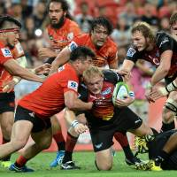 Bulls player Adrian Strauss (center) is tackled by the Sunwolves' Shota Horie (left) during Saturday's Super Rugby match in Singapore. The Bulls defeated the Sunwolves 30-27. | AFP-JIJI