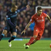 Liverpool's Roberto Firmino (right) vies for the ball with Manchester City's Fernando on Wednesday night at Anfield. | AP