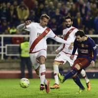 Barcelona's Lionel Messi scores past Rayo Vallecano's Quini in Spanish League action on Thursday night. Barca won 5-1.   AFP-JIJI