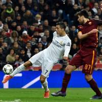 Madrid's Cristiano Ronaldo (left) kicks the ball as he competes against Roma defender Ervin Zukanovic on Tuesday. | AFP-JIJI