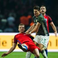 England's Eric Dier (left) and Germany's Mario Gomez compete for the ball in Berlin on Saturday. England won 3-2. | AFP-JIJI