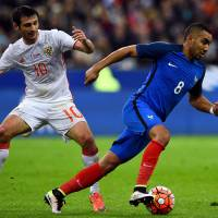 France's Dimitri Payet (right) takes the ball past Russia's Alan Dzagoev at the Stade de France on Tuesday. | AFP-JIJI