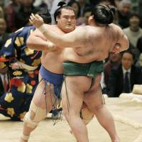 Kotoshogiku (left) pushes Takayasu out of the ring on the first day of the Spring Grand Sumo Tournament in Osaka on Sunday. | KYODO