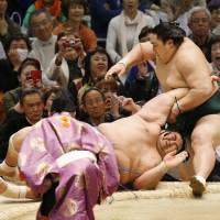 Second-ranked maegashira Okinoumi earns his first victory of the Spring Grand Sumo Tournament in Osaka by overpowering ozeki Kotoshogiku on Thursday. | KYODO