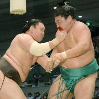 Hakuho (left) tussles with a bloodied Yoshikaze during their bout at the Spring Grand Sumo Tournament on Sunday in Osaka. | KYODO