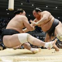 Toyonoshima (right) outmuscles Harumafuji on Tuesday at the Spring Grand Sumo Tournament in Osaka. | KYODO