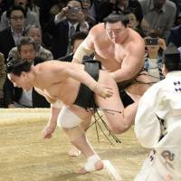 Hakuho (right) sends Harumafuji out of the ring on the final day of the Spring Grand Sumo Tournament in Osaka on Sunday. | KYODO