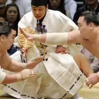 Hakuho (right) reaches out with his hand at the start of his bout against Harumafuji at the Spring Grand Sumo Tournament in Osaka on Sunday. | KYODO
