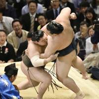 Yokozuna Hakuho (left) wrestles with ozeki Kisenosato during their bout on Wednesday in Osaka. | KYODO