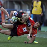 The Sunwolves' Akihito Yamada (right) tackles Jaco van der Walt of the Lions during the Sunwolves' Super Rugby debut at Prince Chichibu Memorial Ground last Saturday. | REUTERS