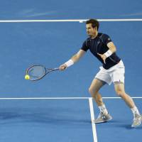 Britain's Andy Murray hits a shot as his brother Jamie looks on during their doubles match against Yoshihito Nishioka and Yasutaka Uchiyama on Saturday. | REUTERS