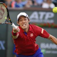 Kei Nishikori stretches for a shot from John Isner in their fourth-round match at the BNP Paribas Open on Wednesday. | AP