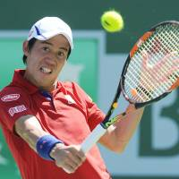 Kei Nishikori plays a shot from Rafael Nadal in their quarterfinal match at the BNP Paribas Open on Friday. Nadal won 6-4, 6-3. | KYODO