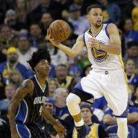 Golden State's Stephen Curry looks to pass while guarded by Orlando's Elfrid Payton in the first half on Monday night. The Warriors beat the Magic 119-113. | AP