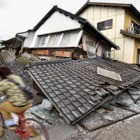 A boy cycles by collapsed house in Aso, Kumamoto, which was jolted by a strong quake early Saturday morning.  | KYODO