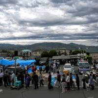 Local residents wait in line for food and goods at a distribution center in Mashiki, Kumamoto Prefecture as storm clouds gather on Saturday. | AP