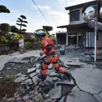 A member of a rescue team runs on a cracked street in  Mashiki, Kumamoto Prefecture on Saturday.  | AFP-JIJI