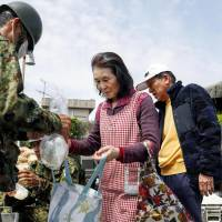 Evacuees receive riceballs from Self Defense Force members in the town of Mashiki, Kumamoto Prefecture, on Saturday.  | KYODO