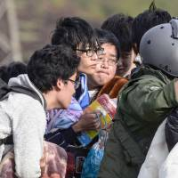 Students from Tokai University receive instructions from a Self Defense Force member before being evacuated by helicopter from the village of Minamiaso, where one of their dormitories reportedly collapsed in the quake, on April 16. | KYODO