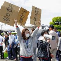 Women direct evacuees to queues for handouts of drinks, sweets and other foods in the town of Mashiki, Kumamoto Prefecture, on April 16.  | KYODO