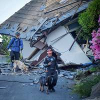Members of rescue team and their dogs patrol the homes around Mashiki, Kumamoto Prefecture on Sataurday, following a series of strong earthquakes that began on April 14.  | AFP-JIJI