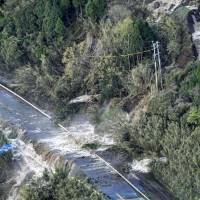 Water dislodged by a landslide pours onto a road in Kitakyushu City on April 16. The tracks of the JR Hohi Line, which runs beside the road, were also washed away.  | KYODO