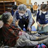 A doctor tends to an elderly woman at an evacuation center in the town of Mashiki, Kumamoto Prefecture, on April 16.  | KYODO